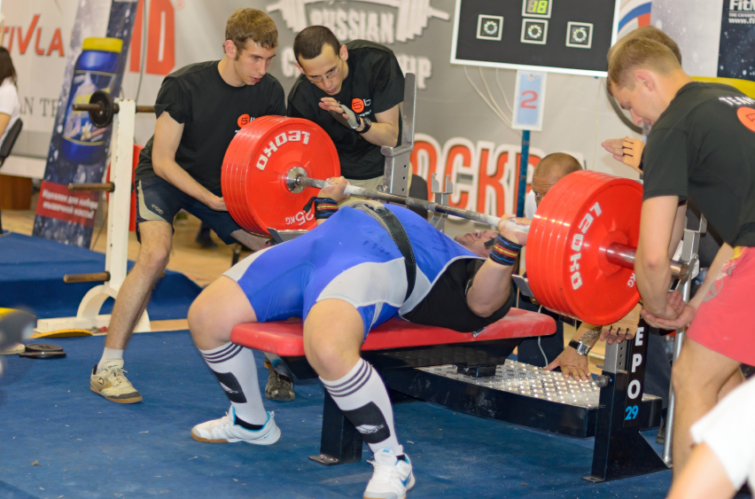 3x3 Powerlifting Program: Low Rep Strength--man pressing with 3 other men spotting him
