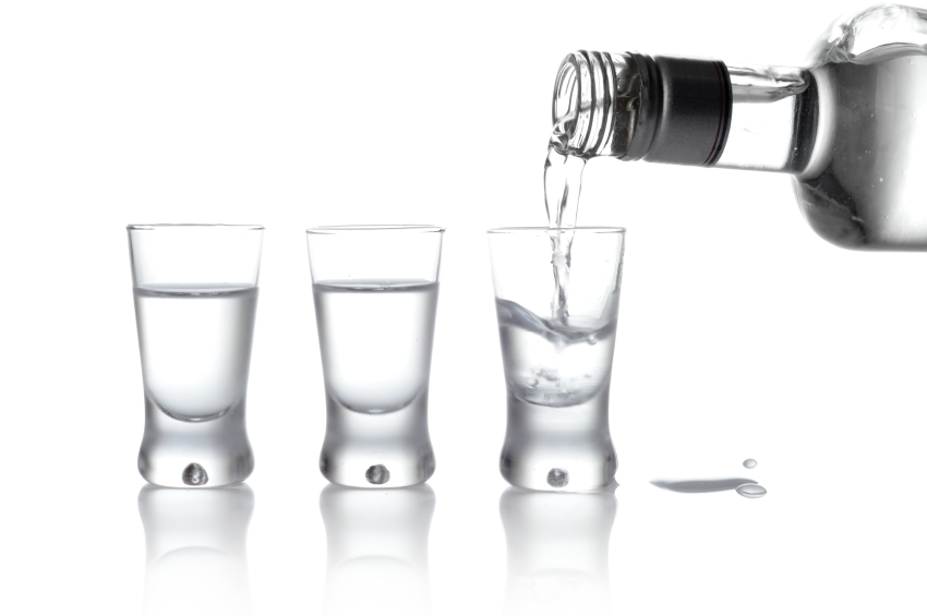 Bottle and glasses of vodka poured into a glass isolated on white